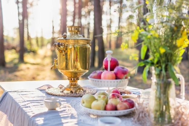 Russischer samowar mit tassen auf einem tisch mit äpfeln und feldblumenstrauß