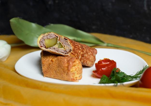 Russischer snack blinchik mit fleisch und mariniertem essen