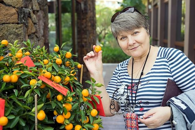 Russischer tourist in der nähe von mandarinen-weihnachtsbaum mandarinente in seiner hand