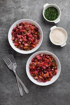Russischer traditioneller salat mit rote beete, kartoffel, karotte, gurke, erbse, salz, dill und öl dressing auf dunkelgrauer oberfläche