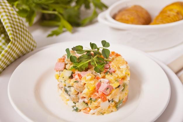 Russischer traditioneller salat olivier mit gemüse und fleisch in der weißen platte.