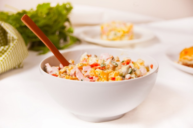 Russischer traditioneller salat olivier mit gemüse und fleisch in der weißen schüssel.