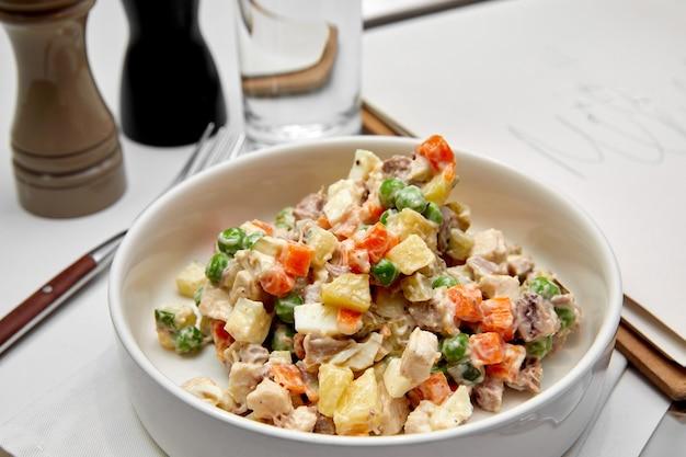 Russischer traditioneller salat olivier mit gemüse und fleisch.