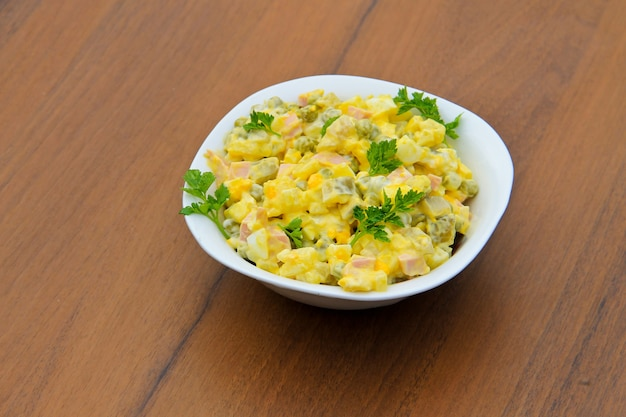Russischer traditioneller salat olivier mit grüner erbse, eiern, eingelegten gurken, kartoffeln, würstchen und mayonnaise auf holztisch