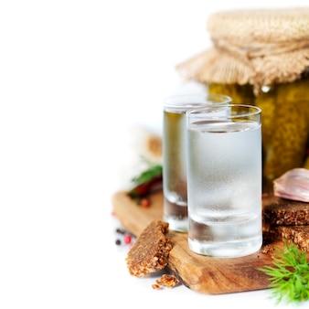Russischer wodka mit traditionellem schwarzbrot und gurken