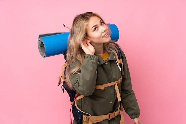 Russisches bergsteigermädchen des teenagers mit einem großen rucksack auf rosa wand, die etwas hört, indem man hand auf das ohr legt
