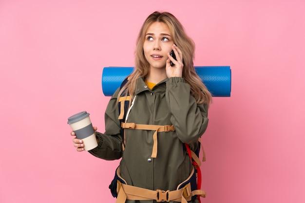 Russisches bergsteigermädchen des teenagers mit einem großen rucksack auf rosa wand, die kaffee zum mitnehmen und ein handy hält