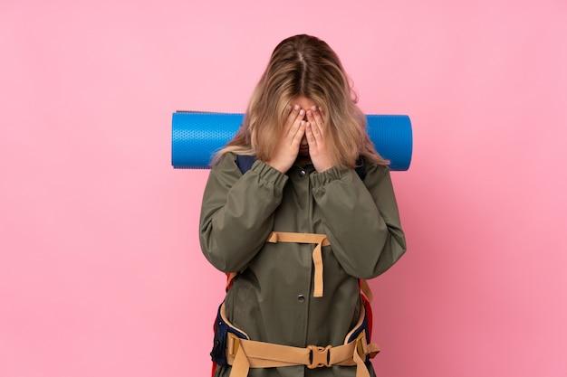 Russisches bergsteigermädchen des teenagers mit einem großen rucksack auf rosa wand mit müdem und krankem ausdruck