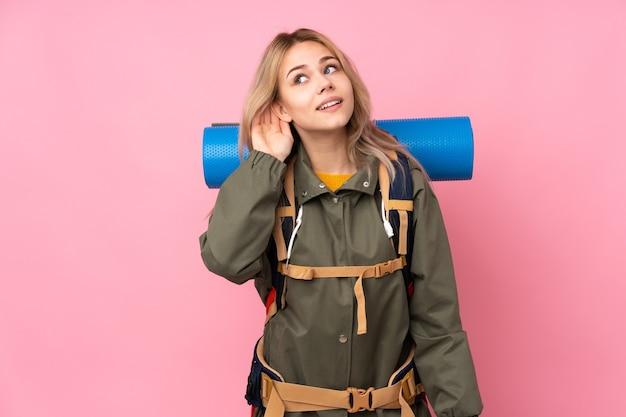 Russisches bergsteigermädchen des teenagers mit einem großen rucksack lokalisiert auf rosa, der etwas hört, indem man hand auf das ohr legt