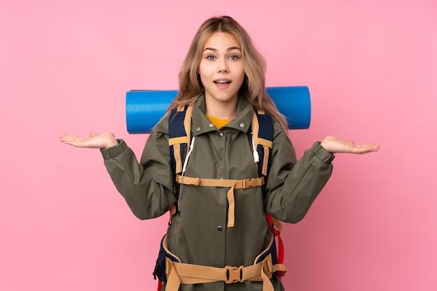 Russisches bergsteigermädchen des teenagers mit einem großen rucksack lokalisiert auf rosa mit schockiertem gesichtsausdruck