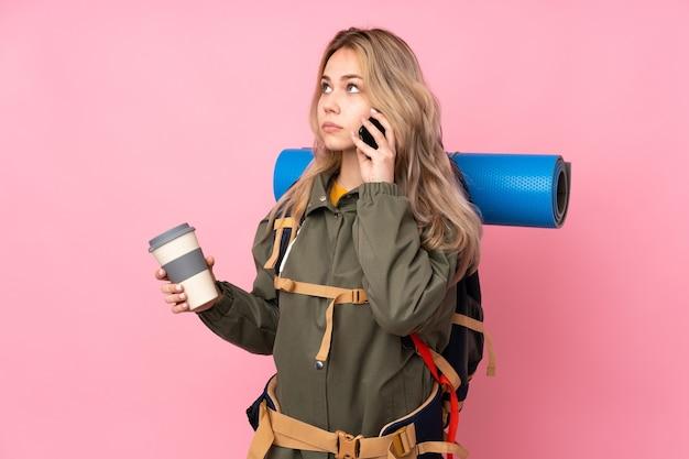 Russisches bergsteigermädchen des teenagers mit einem großen rucksack lokalisiert auf rosa wand, die kaffee zum mitnehmen und ein handy hält