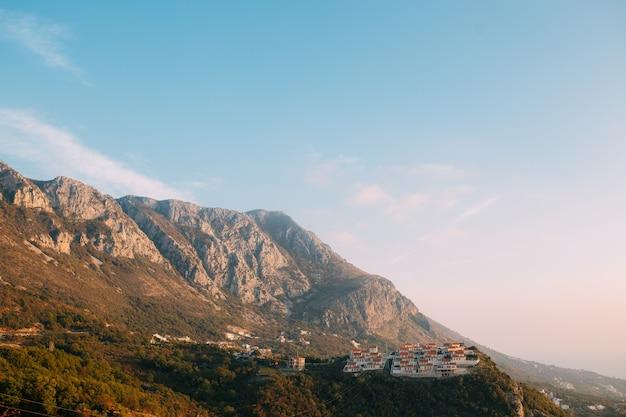 Russisches dorf auf dem berg in montenegro über der insel sveti stefan.