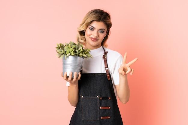 Russisches gärtnermädchen, das eine pflanze lokalisiert auf rosa lächelnd hält und siegeszeichen zeigt