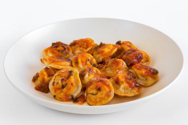 Russisches lebensmittel pelmeni, gebratene fleischmehlklöße auf weißer platte, mit tomatensauce