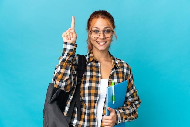 Russisches mädchen der teenager-studentin auf blau, das eine große idee aufzeigt