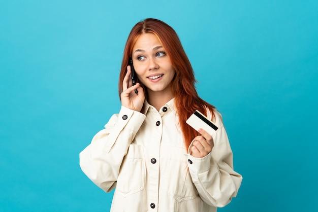 Russisches mädchen des teenagers auf blau, das ein gespräch mit dem mobiltelefon hält und eine kreditkarte hält