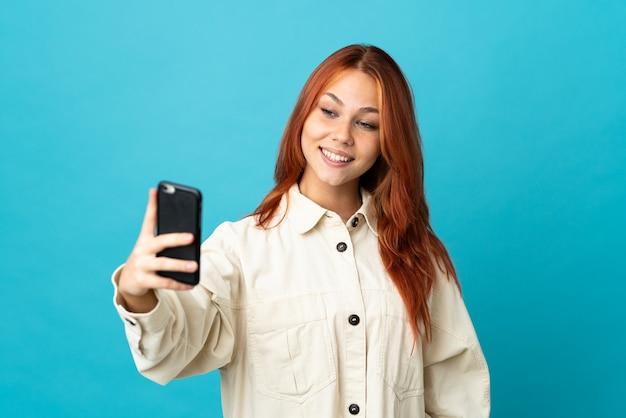 Russisches mädchen des teenagers auf blau, das ein selfie mit handy macht