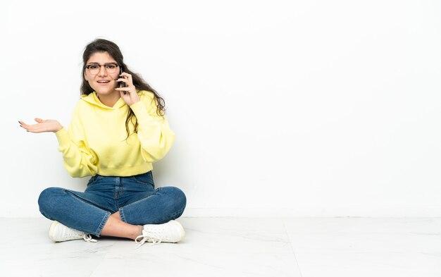 Russisches mädchen des teenagers, das auf dem boden sitzt und ein gespräch mit dem mobiltelefon mit jemandem hält