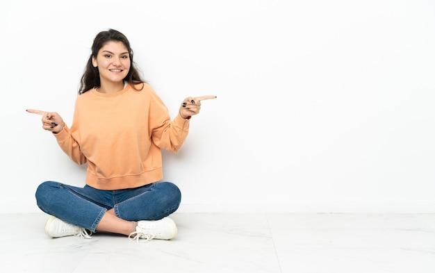 Russisches mädchen des teenagers, das auf dem boden sitzt und finger auf die seiten zeigt und glücklich ist