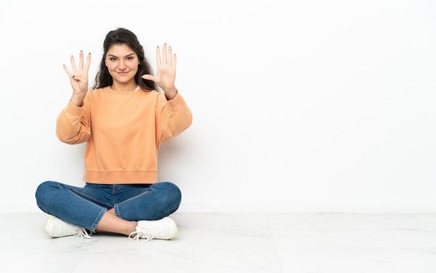 Russisches mädchen des teenagers, das auf dem boden sitzt und neun mit den fingern zählt