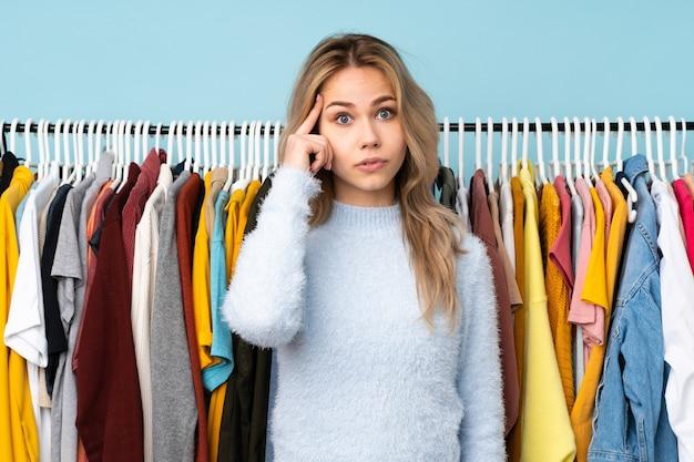 Russisches mädchen des teenagers, das einige kleider kauft, die auf blau lokalisiert denken eine idee
