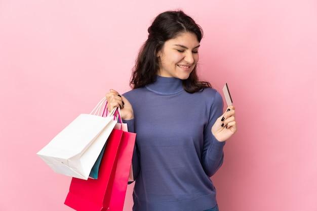 Russisches mädchen des teenagers lokalisiert auf rosa, das einkaufstaschen und eine kreditkarte hält