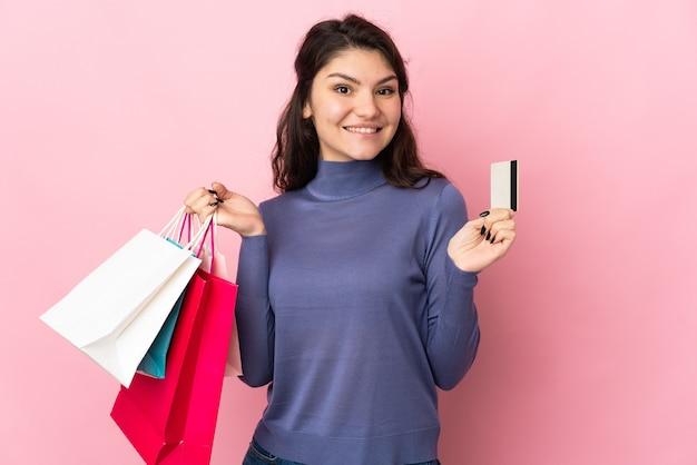 Russisches mädchen des teenagers lokalisiert auf rosa wand, die einkaufstaschen und eine kreditkarte hält