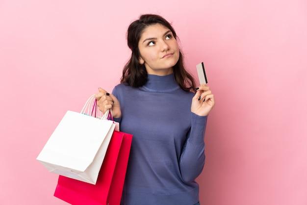 Russisches mädchen des teenagers lokalisiert auf rosa wand, die einkaufstaschen und eine kreditkarte und das denken hält