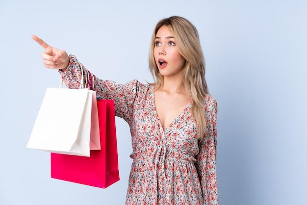 Russisches mädchen des teenagers mit einkaufstasche lokalisiert auf blau wegweisend