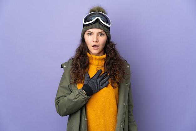 Russisches mädchen des teenagers mit snowboardbrille lokalisiert auf lila hintergrund überrascht und schockiert, während sie nach rechts schaut