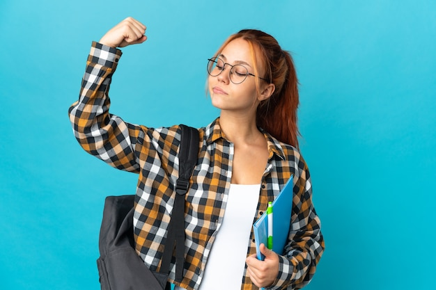 Russisches mädchen des teenagerschülers auf blau, das starke geste tut