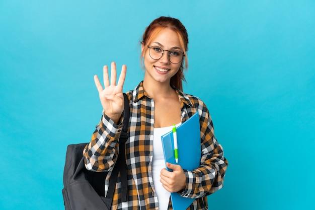 Russisches mädchen des teenagerschülers auf blau glücklich und zählt vier mit den fingern
