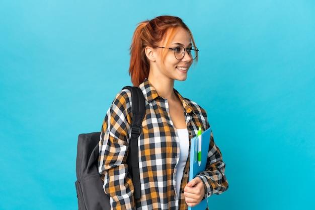 Russisches mädchen des teenagerschülers auf der blau aussehenden seite