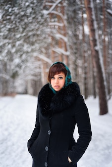 Russisches mädchen im mantel und im schal im kalten winter