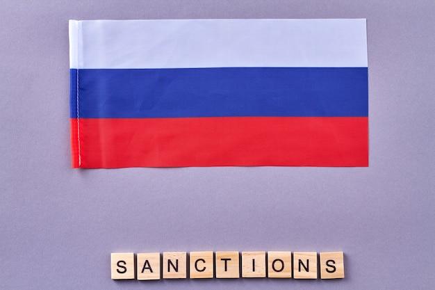 Russisches sanktionskonzept. holzwürfel auf lila hintergrund.