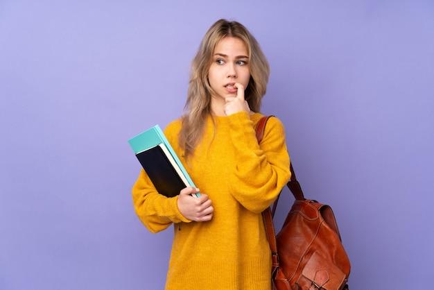 Russisches studentenmädchen des teenagers auf lila wand nervös und ängstlich