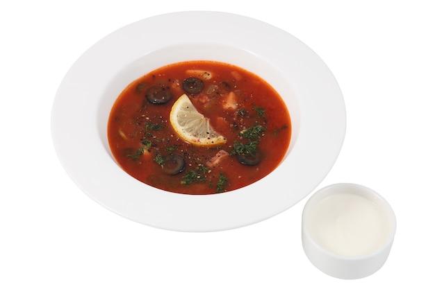 Russisches suppensalzkraut in der runden platte, lokalisiert auf weißem hintergrund.
