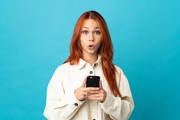 Russisches teenager-mädchen auf blau, das die kamera beim verwenden des handys mit überraschtem ausdruck betrachtet