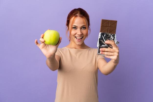 Russisches teenager-mädchen auf purpur, das eine schokoladentafel in einer hand und einen apfel in der anderen nimmt