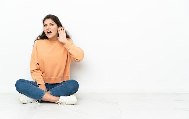 Russisches teenager-mädchen, das auf dem boden sitzt und etwas hört, indem es hand auf das ohr legt