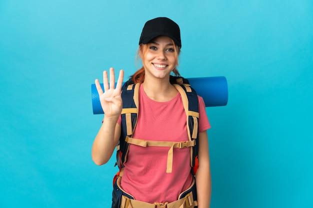 Russisches wandermädchen des teenagers auf blau glücklich und zählt vier mit den fingern