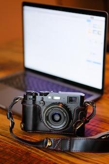 Russland, tjumen, 02.12.2019. eine fujifilm-kamera in einem schwarzen ledertasche auf einem dunklen holztisch. neben dem laptop. arbeitsplatz und zubehör des fotografen oder eines freiberuflers. kopieren text einfügen.