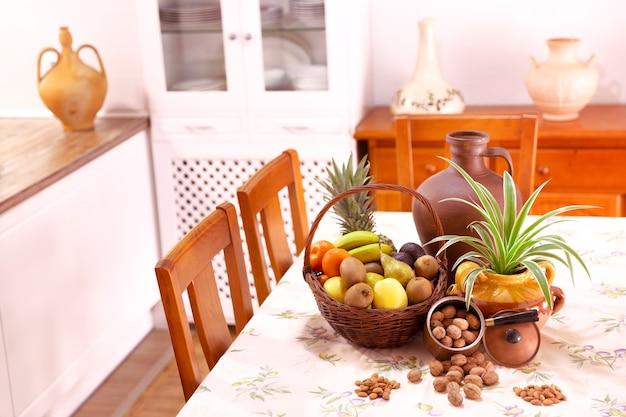 Rustikale designküche mit korb mit früchten, pflanzen und nüssen auf dem tisch. dekorationskonzept.