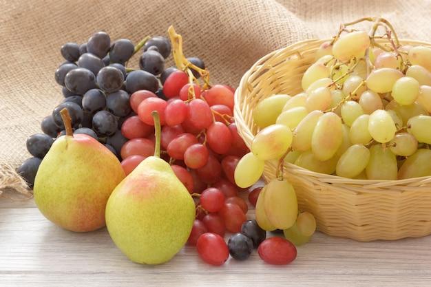 Rustikale fruchtbirnen und -trauben auf weißem holztisch
