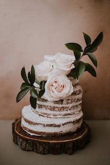 Rustikale hochzeitstorte mit drei weißen rosen topper auf braunem textur hintergrund
