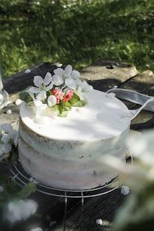 Rustikale hochzeitstorte mit weißen lila blumen