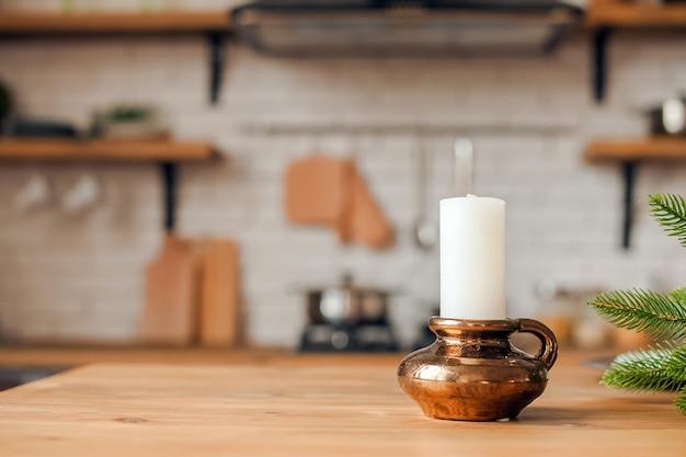 Rustikale küche in unschärfe. tabelle und kerze in einem bronzekerzenhalter im fokus.
