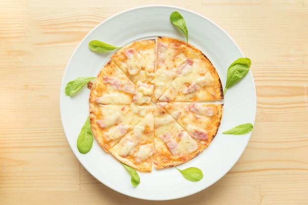 Rustikale pizza auf hölzernem hintergrund. ansicht von oben