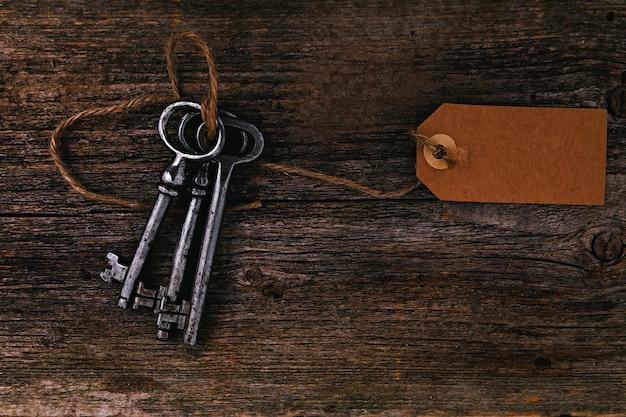 Rustikale schlüssel mit aufkleber auf holztisch