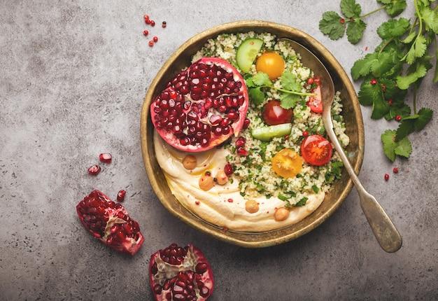 Rustikale schüssel mit couscous-salat mit gemüse, hummus und frisch geschnittenem granatapfel. mahlzeit im nahöstlichen oder arabischen stil mit gewürzen und frischem koriander. gesundes mediterranes abendessen, getöntes bild